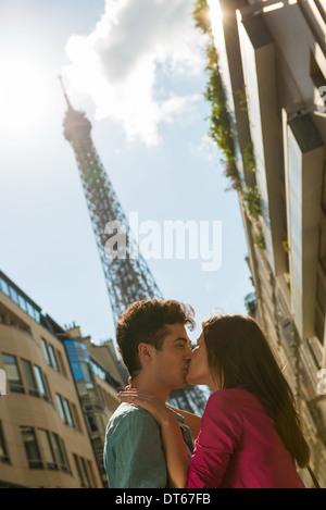 Jeune couple partageant un baiser en face de la Tour Eiffel, Paris, France Banque D'Images