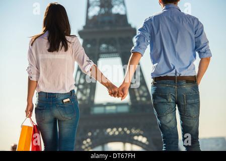 Jeune couple strolling en face de la Tour Eiffel, Paris, France Banque D'Images