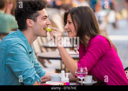 Jeune couple de manger au Café de la chaussée de macarons, Paris, France Banque D'Images