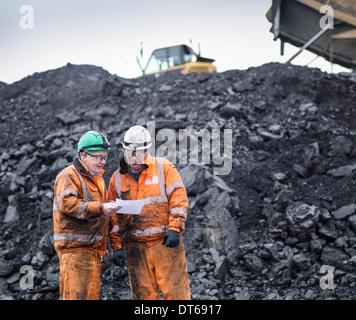 Travailleurs en discussion devant les stocks de charbon dans la mine de charbon Banque D'Images