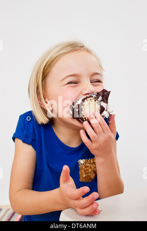 Studio portrait of young girl eating chocolate marshmallow Banque D'Images