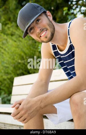 Portrait de jeune joueur de basket-ball masculin assis sur banc de parc Banque D'Images