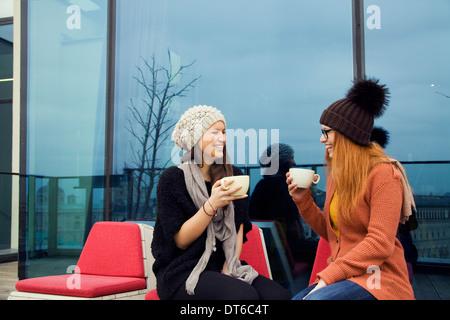 Deux jeunes femmes adultes appréciant café sur toit-terrasse Banque D'Images