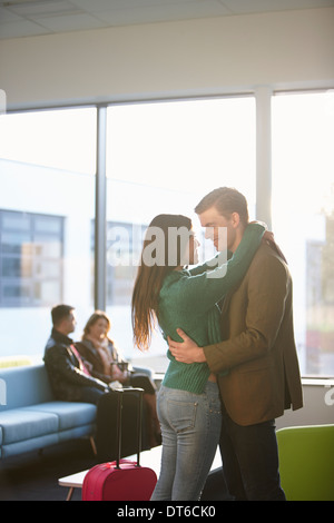 Jeune couple hugging in airport Banque D'Images