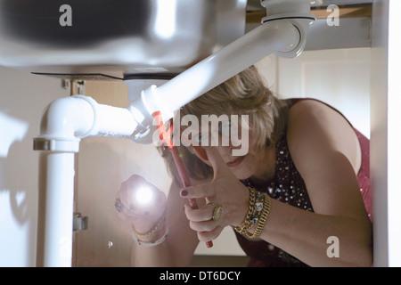 Senior woman in evening wear fixant tuyaux sous l'évier de cuisine Banque D'Images