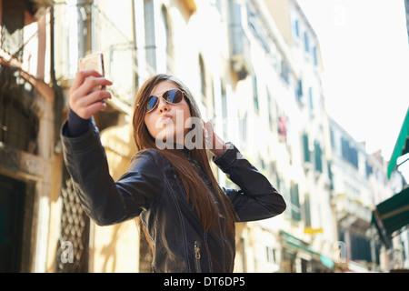 Girl taking sur smartphone selfies, Venise, Italie