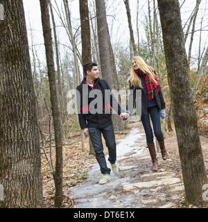 Un couple marche main dans la main à travers un bois en hiver. Banque D'Images