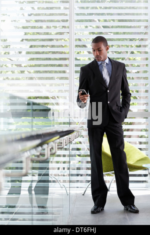 Woman texting on mobile phone in office Banque D'Images