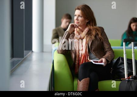 Femme mature en salle d'embarquement Banque D'Images