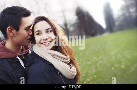 Cute young couple appréciant chaque compagnie d'autres personnes. Young man and woman outdoors in park avec copyspace. Banque D'Images