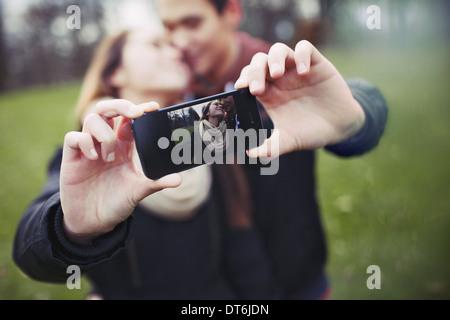 Teenage romantique couple taking self portrait with cell phone au parc. Jeune homme et femme dans l'amour. Banque D'Images