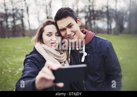 Drôle de couple photographing themselves with smart phone dans le parc. Jolie jeune fille avec son petit ami à prendre Banque D'Images