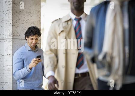 Trois personnes sur le trottoir, un homme à l'aide de son téléphone mobile, un homme dans un imperméable, et un Banque D'Images