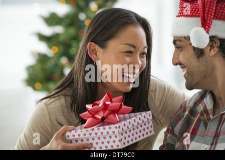 Un homme dans un chapeau de Père Noël. À la maison. Décoré d'un arbre de Noël. Banque D'Images