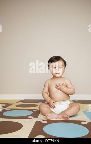 Un jeune garçon bébé 8 mois portant des couches en tissu. Banque D'Images