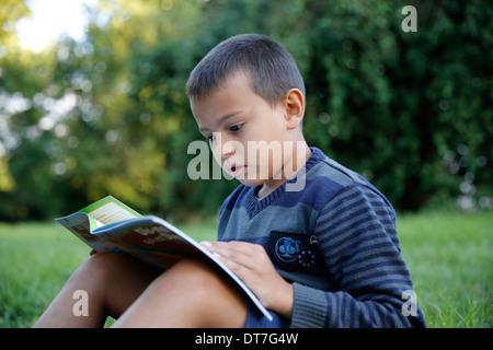 Garçon de 7 ans la lecture d'un livre chrétien dans un jardin Banque D'Images