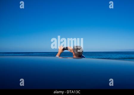 Vue arrière de l'homme de prendre une photo de vue sur l'Océan Banque D'Images