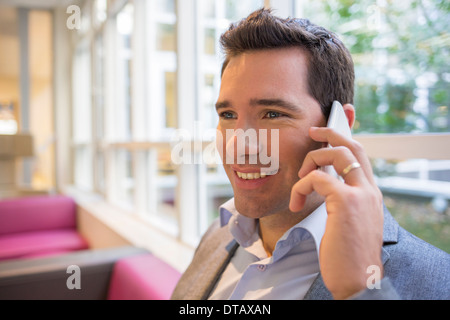 Happy smiling young woman on phone in office Banque D'Images