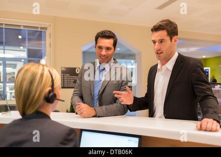 La communication avec les hommes d'affaires dans le hall réceptionniste femme Banque D'Images
