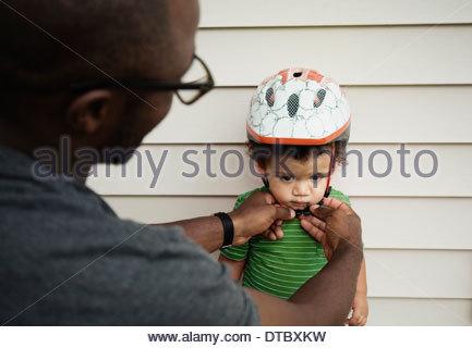 Père de mettre sur casque pour fils Banque D'Images