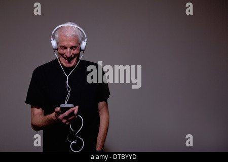 Portrait of senior man wearing headphones et à l'aide de MP3 player Banque D'Images