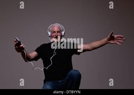 Portrait of senior man au format MP3 sur le casque Banque D'Images