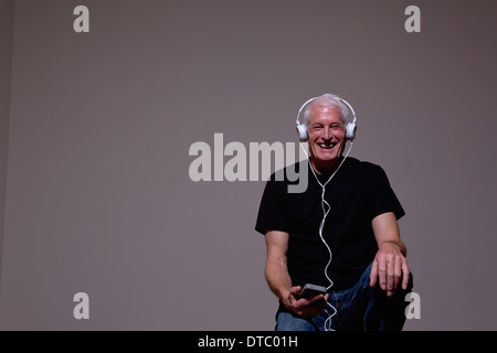 Portrait of senior man listening to MP3 player sur le casque Banque D'Images
