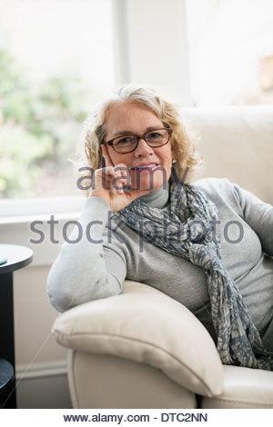 Portrait of senior woman sitting on sofa Banque D'Images