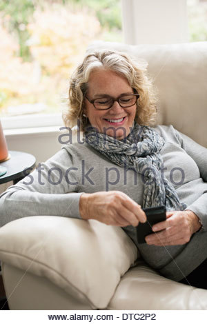 Ambiance senior woman sitting on sofa using mobile phone Banque D'Images
