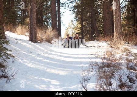 Garçon et les jeunes adultes de la luge dans la forêt enneigée Banque D'Images