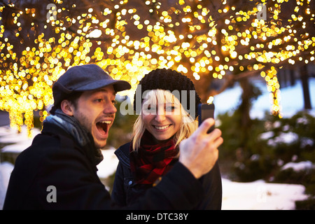 Young couple taking self portrait with outdoor xmas lights Banque D'Images