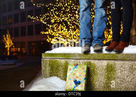 Les jambes de jeune couple debout sur un mur couvert de neige en ville Banque D'Images