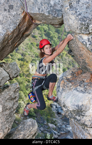 Young female rock climber climbing rock face Banque D'Images