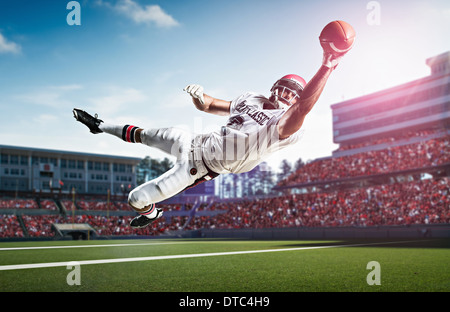 American football player catching ball mid air dans le stade Banque D'Images