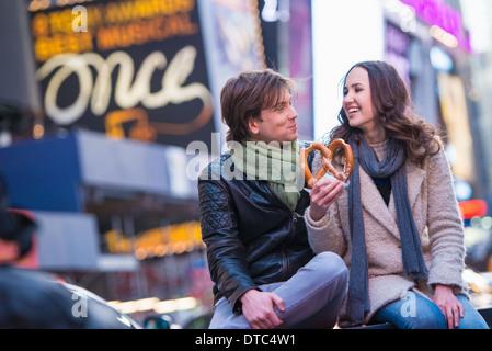 Jeune couple partage pretzel, New York City, USA