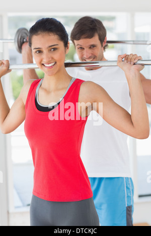 Fit young man and woman lifting barbells Banque D'Images