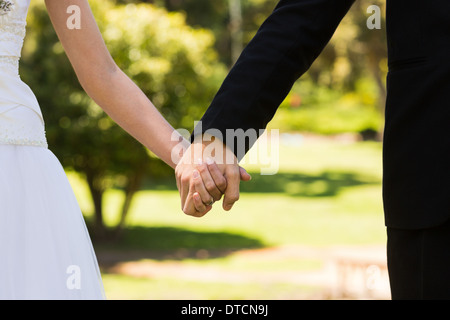 Mid section of senior couple holding hands in park Banque D'Images