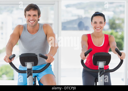 Smiling young couple working out at spinning class Banque D'Images