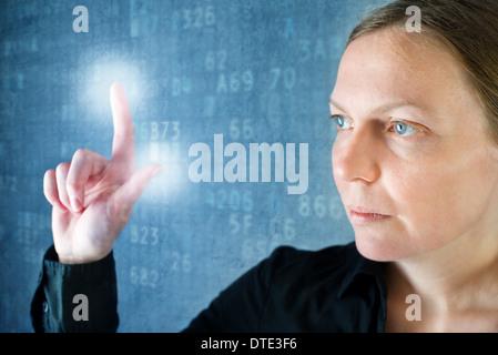 Attractive businesswoman en appuyant sur le bouton de l'écran tactile, de la technologie moderne concept. Banque D'Images