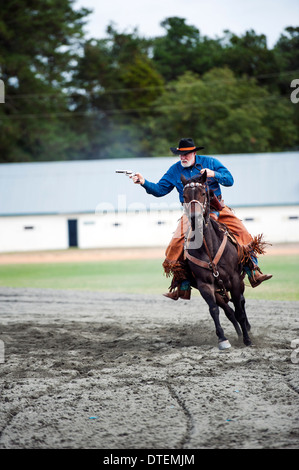 Un cow-boy sur un cheval au grand galop, pistolet tiré. Annie Oakley Jours Boom Festival à Pinehurst en Caroline Banque D'Images