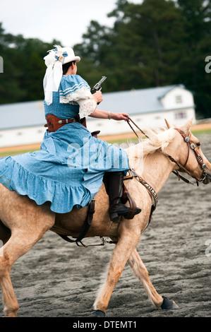 Une cowgirl sur un cheval au grand galop, pistolet tiré. Annie Oakley Jours Boom Festival à Pinehurst en Caroline Banque D'Images