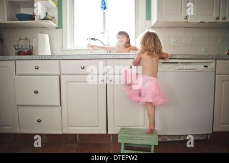 Les filles (2-3, 4-5) baignant dans un évier de cuisine Banque D'Images