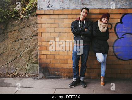 Beau jeune homme et femme de vêtements chauds se tenant ensemble s'appuyant sur un mur extérieur. Teenage Asian Banque D'Images
