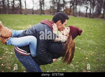 Beau jeune homme portant sa jolie petite amie et s'embrasser. Mixed Race couple dans l'amour en plein air dans le Banque D'Images