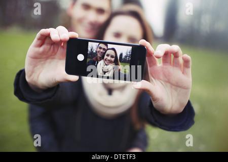 Young couple taking a self-portrait avec un smartphone au parc. Mixed Race woman l'homme et de la femme à l'extérieur. Banque D'Images