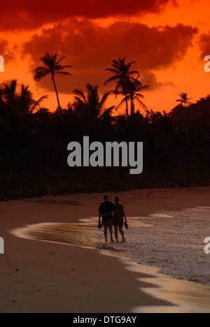 Couple en train de marcher sur la plage au coucher du soleil à Long Bay, Tortola, British Virgin Islands. Banque D'Images