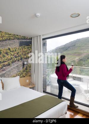 Femme à la recherche de grande fenêtre tenant un verre de vin rouge