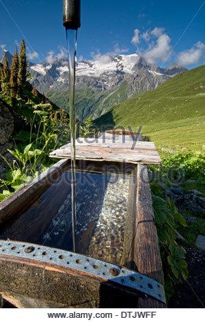 Verser de l'eau de source de montagne fontaine dans les montagnes françaises du Parc National de la Vanoise, France Banque D'Images