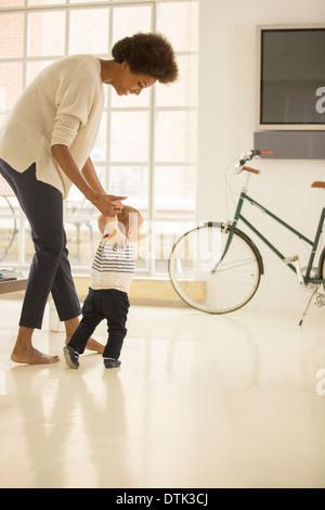 Mother helping baby boy à pied dans la salle de séjour Banque D'Images