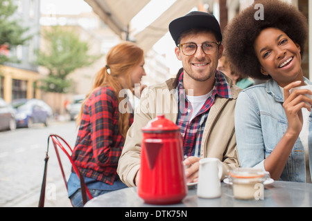 Couple drinking coffee at sidewalk cafe Banque D'Images